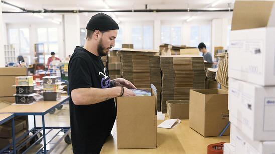 Der Boom im Onlinehandel lässt wieder nach: ein Mitarbeiter eines Onlinehändlers verpackt ein Päckli (Archivbild).